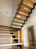 Glass staircase. Ash wood, metal and glass staircase in a contemporary interior stock photography