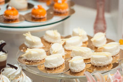 Glass stand with cupcakes on a wedding candy bar table Royalty Free Stock Photo