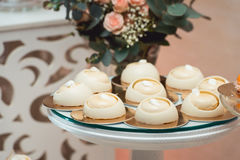 Glass stand with cupcakes on a wedding candy bar table Stock Images