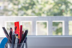Glass with stationery. On light blurred background Royalty Free Stock Image