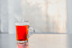 A glass of steaming hot tea on the table against the window Royalty Free Stock Photo