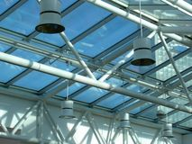 Glass and steel ceiling with lights. Glass and steel interior of building with sunlight and shadows Royalty Free Stock Photos