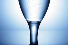Glass stemware. A close up of a stemware glass on a blue background Royalty Free Stock Image