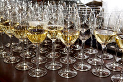 Glass stemware and wine. Restaurant glass stemware with white wine on a black table Stock Images