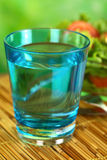Glass of Still Mineral Water. With fresh salad in the back (Selective Focus, Focus on the front rim of the glass Stock Photos