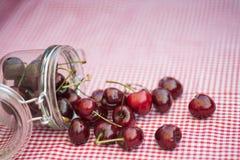 Glass storage jar full of fresh cherries Stock Photo