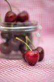 Glass storage jar full of fresh cherries Stock Image
