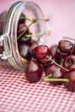 Glass storage jar full of fresh cherries Stock Photos