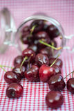 Glass storage jar full of fresh cherries Royalty Free Stock Image