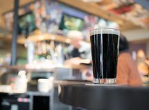 Glass of Stout beer on wooden table. In pub background Royalty Free Stock Images