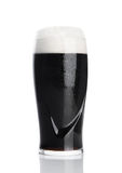 Glass of stout dark beer with foam and dew. On white background Stock Images