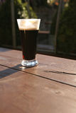 Glass of stout, summer evening Stock Image