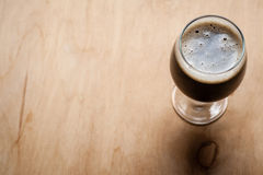 Glass of stout on wood Royalty Free Stock Photos