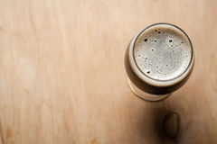 Glass of stout on wood Royalty Free Stock Photography
