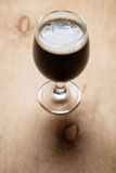 Glass of stout on wood Royalty Free Stock Photo