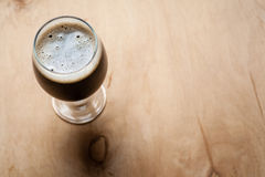 Glass of stout on wood Stock Photo