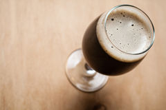 Glass of stout on wood Stock Photography