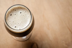 Glass of stout on wood Stock Images