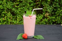 Glass of strawberries, cherries smoothie with straw on wooden table. Protein cocktail. Healthy drink. Fresh homemade smoothie. Hea. Lthy breakfast stock images
