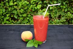 Glass of strawberries, peach smoothie with straw on wooden table. Protein cocktail. Healthy drink. Fresh homemade smoothie. Health Royalty Free Stock Photo