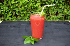 Glass of strawberries, peach smoothie with straw on wooden table. Protein cocktail. Healthy drink. Fresh homemade smoothie. Health Stock Image