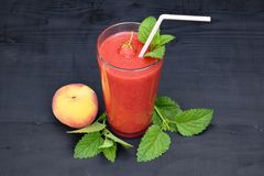 Glass of strawberries, peach smoothie with straw on wooden table. Protein cocktail. Healthy drink. Fresh homemade smoothie. Health Stock Photography