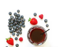 A glass of strawberries, raspberries, blueberries juice isolated on white. A glass of berries juice from strawberries, raspberries, blueberries and ingredients Royalty Free Stock Photos