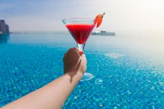 A glass of strawberry cocktail in female hands. Swimming pool. Photo of A glass of strawberry cocktail in female hands. Swimming pool stock images