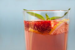 Glass of strawberry lemonade with pieces of strawberry, lemon and fresh mint. Stock Image