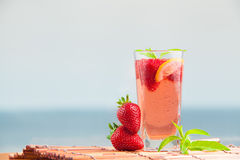 Glass of strawberry lemonade with pieces of strawberry, lemon and fresh mint. Stock Photo