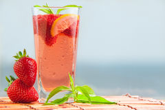 Glass of strawberry lemonade with pieces of strawberry, lemon and fresh mint. Royalty Free Stock Photo