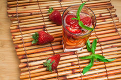 Glass of strawberry lemonade with pieces of strawberry, lemon and fresh mint. Stock Photos