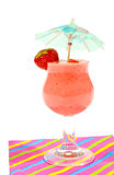 Glass of strawberry smoothie with small parasol Royalty Free Stock Photo