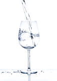 Glass with the stream of dinking water Stock Images