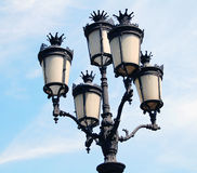 Glass street lanterns against blue sky Stock Images