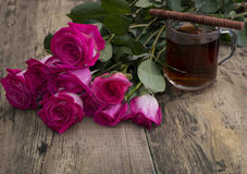 Glass of strong tea, cookies and bouquet of scarlet roses Stock Image