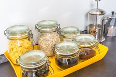 Glass stylish vintage jars with different food in the kitchen. Oatmeal, cornflakes, coffee tea royalty free stock photo