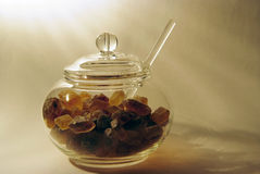 Glass sugar bowl with brown caramelized sugar. In rays of light Royalty Free Stock Photography