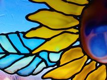 Glass Sunflower. A speckled, textured stained glass sunflower window stock images