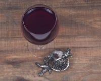 Glass of sweet pomegranate wine and pomegranate shabbat metal decoration Royalty Free Stock Photos