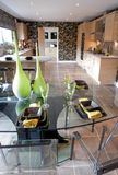 Glass table in kitchen. Modern home kitchen with a fashionable glass table in the foreground Stock Images