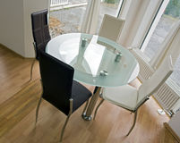 Glass table with leather chairs. Modern glass table with four leather chair positioned in the corner of the dining room Royalty Free Stock Photo