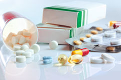 Glass table with pills, blisters and containers. Glass table with white tablets group, blisters and containers Stock Image