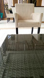 Glass table with plastic weave in front of chair Stock Photo