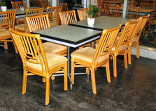 Glass table and wooden chairs Royalty Free Stock Photos