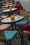 Glass tables of an outdoor cafe with pumpkins and colored cushions of chairs royalty free stock images