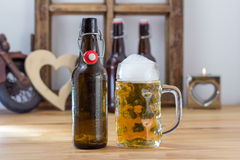 Glass tankard of chilled beer with a bottle. Glass tankard of refreshing frothy chilled beer with an empty unlabeled brown bottle alongside on a wooden counter Royalty Free Stock Photo