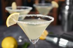 Glass with tasty lemon drop martini cocktail. On blurred background, closeup stock photography