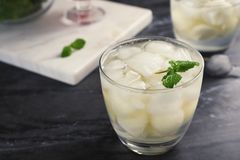 Glass with tasty melon ball drink. On dark table stock photo