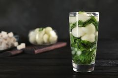 Glass with tasty melon ball drink. On dark table royalty free stock photo